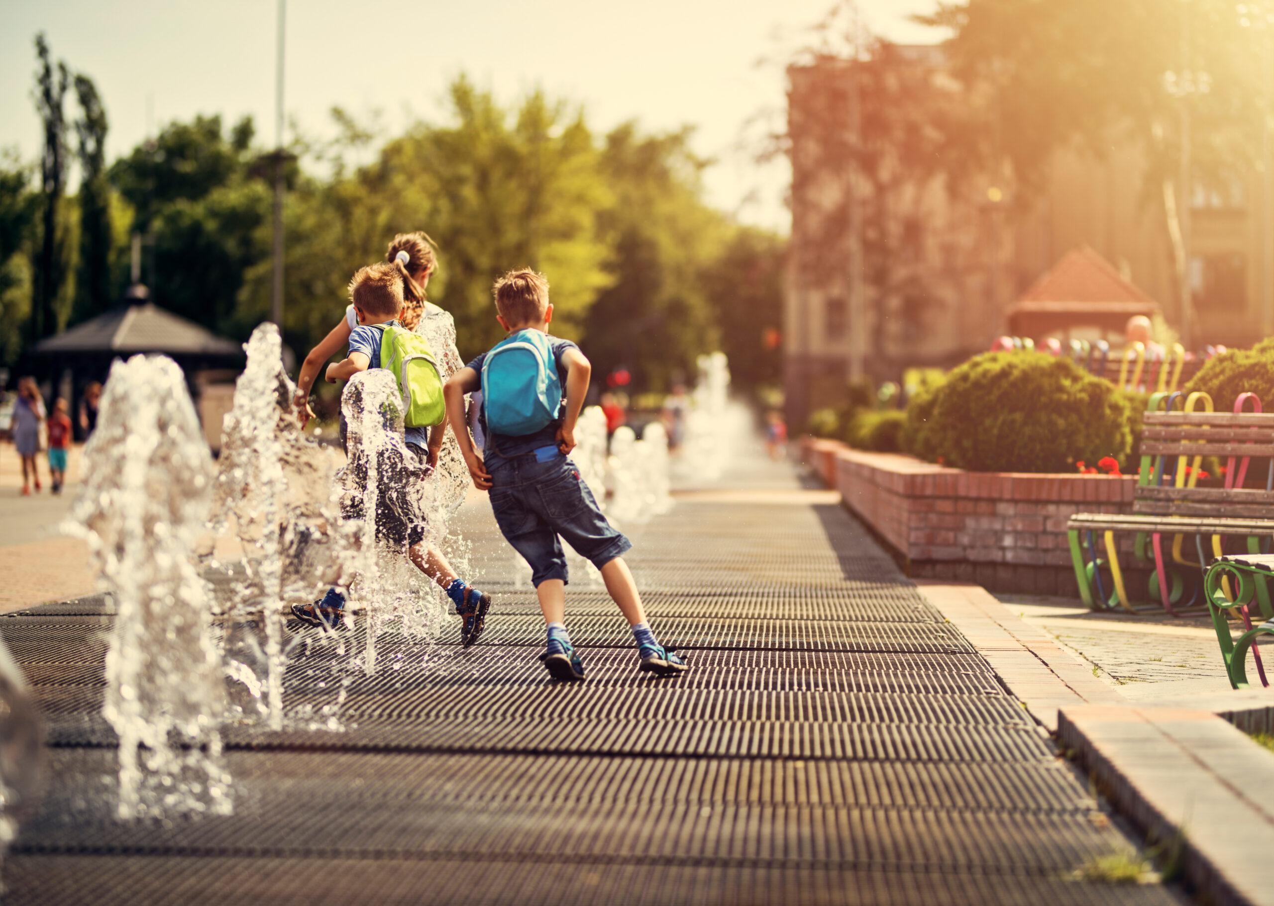 Kids running between fountains on a hot summer day.